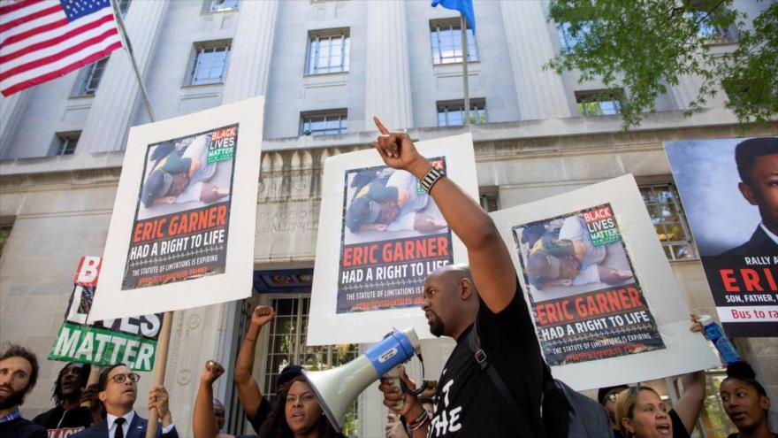 Manifestantes convocan condenar a los autores del asesinato del afroamericano Eric Garner ante el Departamento de Justicia de EE.UU., en Washington.