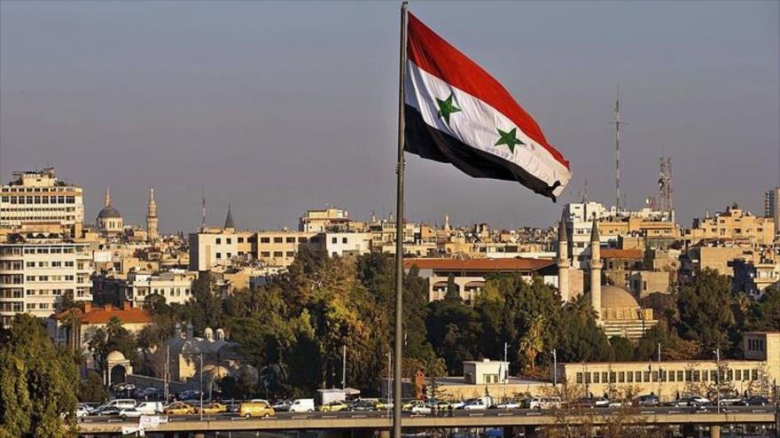 Bandera siria izada en una plaza en Damasco.