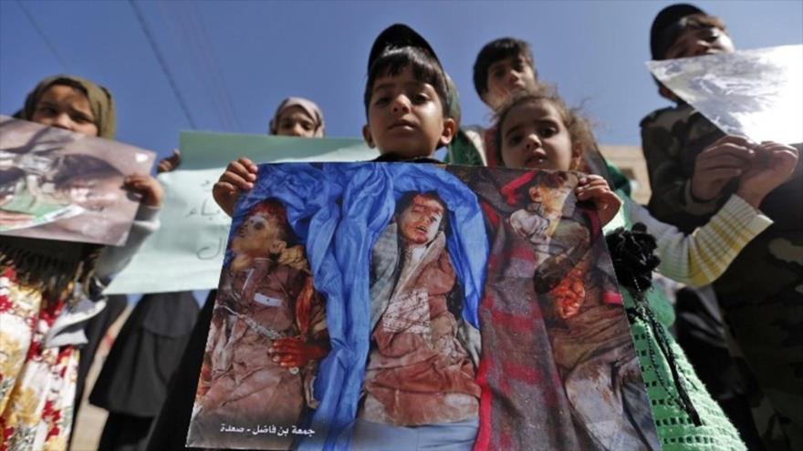 Niños yemeníes llevan fotos de varias víctimas durante la ceremonia de 1000 días de agresión saudí a Yemen, en Saná, 21 de diciembre de 2017.