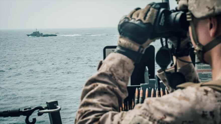 Un marine de EE.UU. observa una nave de ataque rápido iraní desde el buque USS John P. Murtha durante su paso por el estrecho de Ormuz, 18 de julio de 2019.