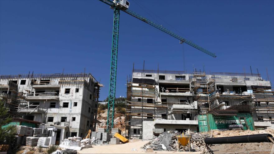 Obreros palestinos trabajan en un sitio de construcción en el asentamiento israelí de Talmon en la Cisjordania ocupada, 31 de julio de 2019. (Foto: AFP)