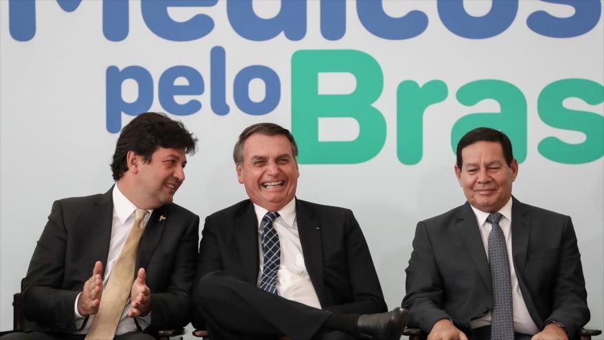 """El presidente de Brasil, Jair Bolsonaro (centro), se ríe en un mitin sobre la denominada iniciativa de su Gobierno, """"Médicos por Brasil"""", 1 de agosto de 2019."""