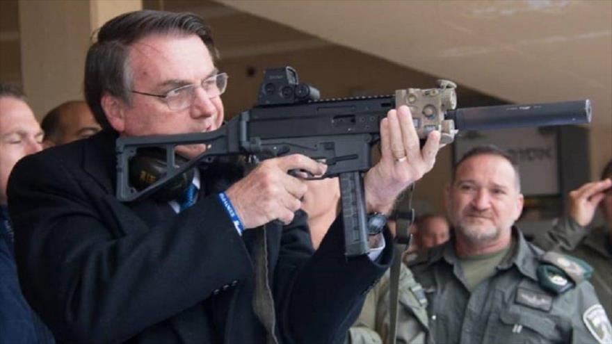 El presidente de Brasil, Jair Bolsonaro,apunta con un fusil.