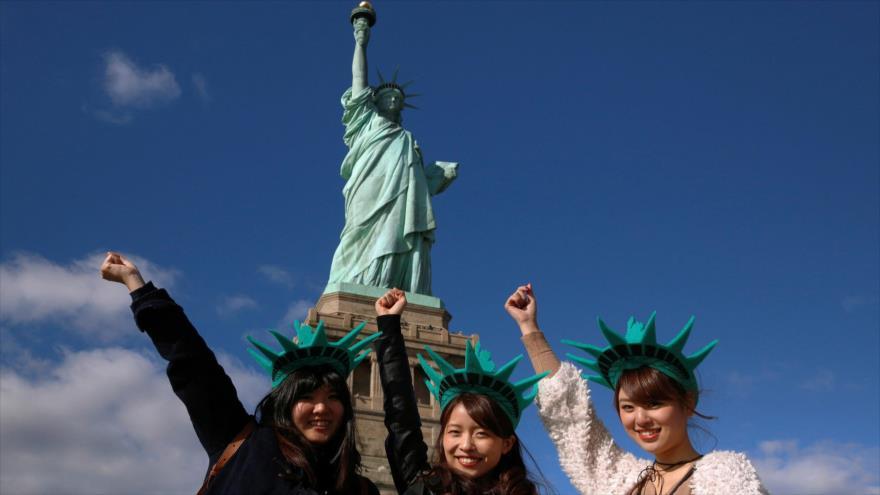 Turistas japonesas en frente de la Estatua de la Libertad de Nueva York, Estados Unidos.