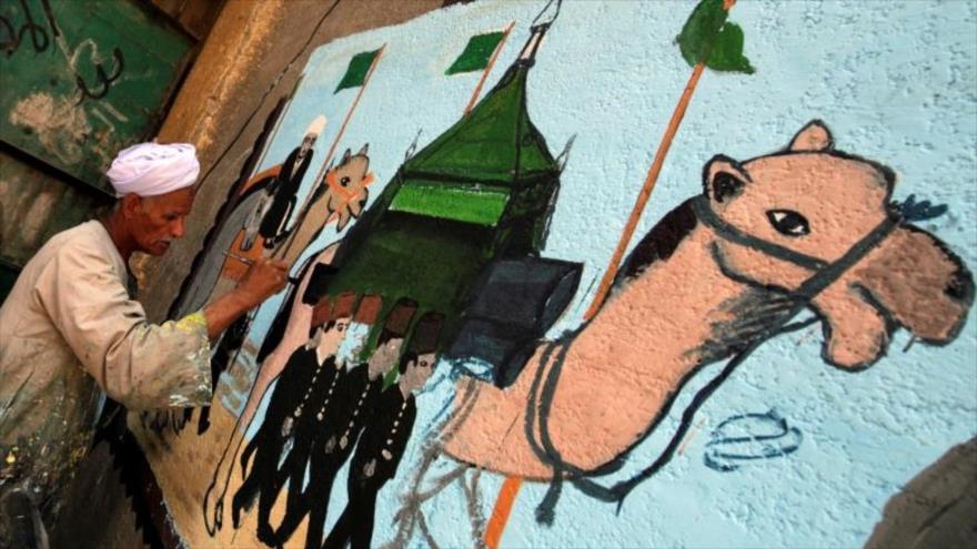 Un artista egipcio pinta murales sobre las paredes de viviendas para celebrar el Hach.