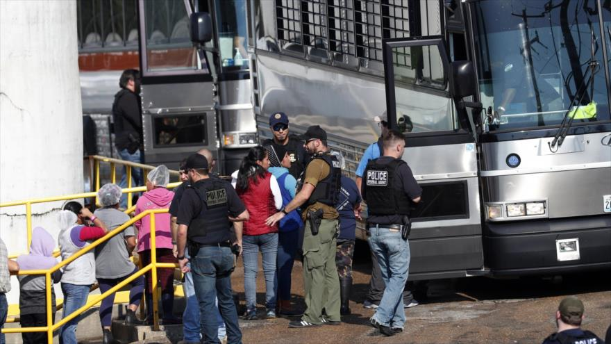Autoridades migratorias de EE.UU. escoltan a un autobús a trabajadores detenidos en una planta de alimentos en Misisipi, 7 de agosto de 2019. (Foto: AP)