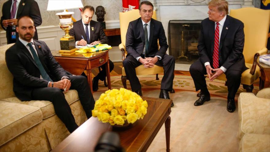El presidente de Brasil, Jair Bolsonaro (c), su hijo Eduardo (izda.) y el mandatario de EE.UU., Donald Trump, Casa Blanca, 19 de marzo de 2019.