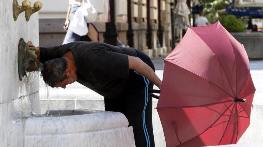 Un hombre se refresca en una fuente en Belgrado a causa del calor que se registra en la zona.