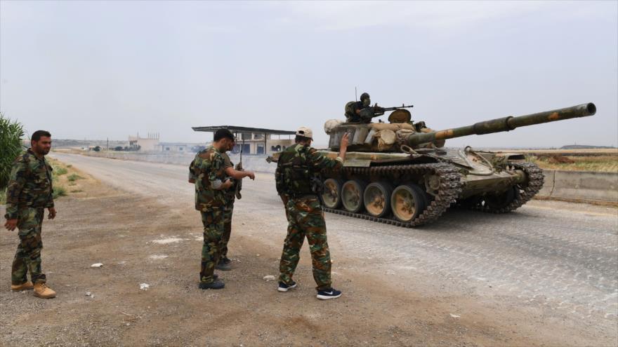 Soldados sirios cerca de un tanque en una carretera en la provincia de Hama durante enfrentamientos con los terroristas, 8 de junio de 2019. (Foto: AFP)