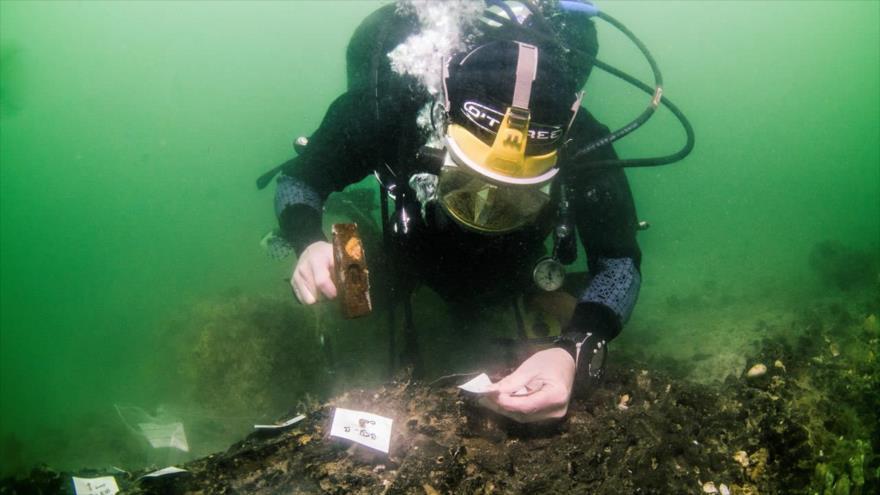 El arqueólogo submarino Garry Momber sobre la plataforma descubierta con un martillo en la mano. (Foto: NOC)
