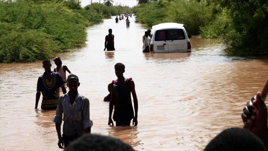 Sudaneses desplazados caminan por una carretera inundada en la aldea de Wad Ramli, en las orillas orientales del río Nilo, 26 de agosto de 2019. (Foto: AFP)