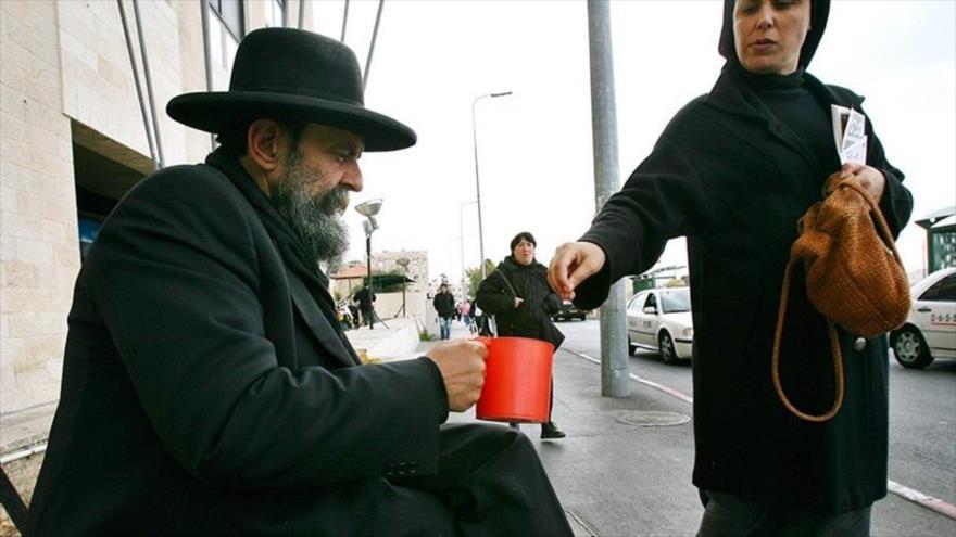 Un mendigo judío recibe limosna de una mujer en Al-Quds (Jerusalén), 26 de marzo de 2006.