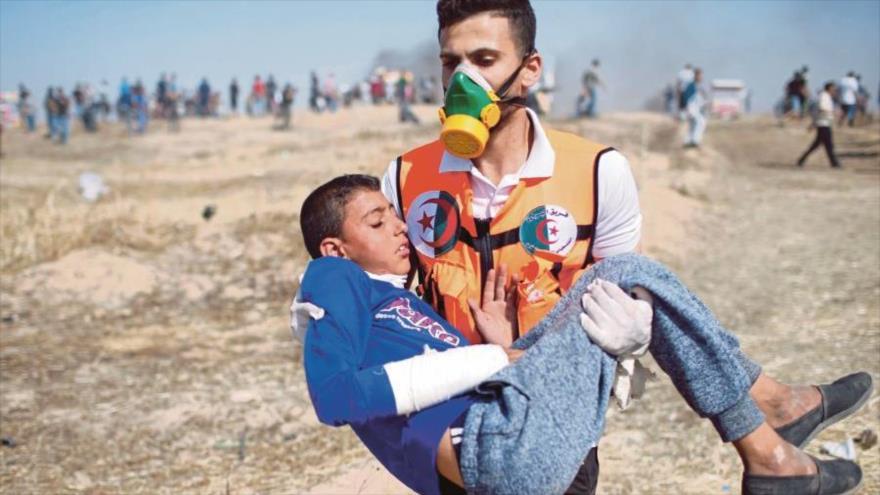 Un médico se lleva a un niño palestino herido en protestas en la Franja de Gaza por fuerzas israelíes.