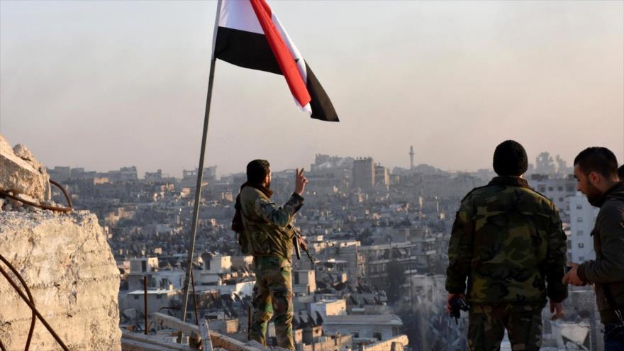 Militares sirios enarbolan la bandera nacional en una localidad liberada en el norte del país.