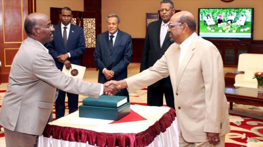 El expresidente sudanés Omar Hasan al-Bashir (dcha.) y el director de su oficina, Hatem Hasan Bejit.
