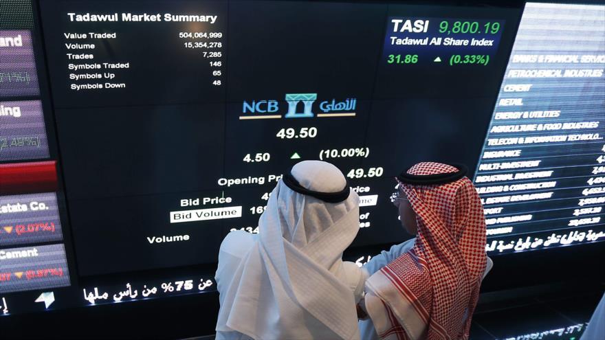 Los inversores saudíes monitorean las acciones en el departamento del mercado cambiario del Banco Comercial Nacional (BCN), 12 de noviembre de 2014.