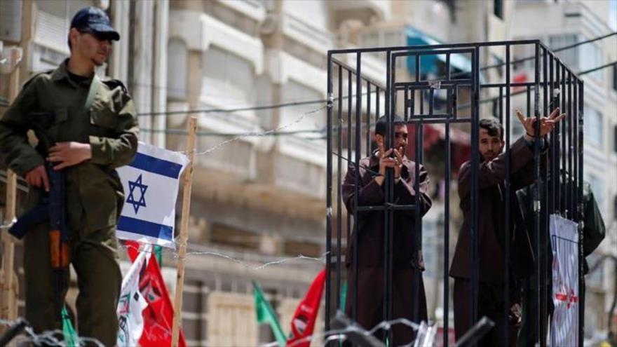 Hombres palestinos fingen ser prisioneros en una cárcel israelí durante una manifestación en la ciudad de Gaza.