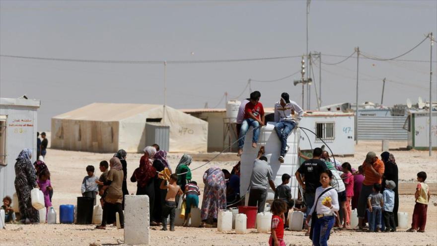 Refugiados sirios hacen cola para obtener agua en el campo de Zaatari cerca de Jordania.