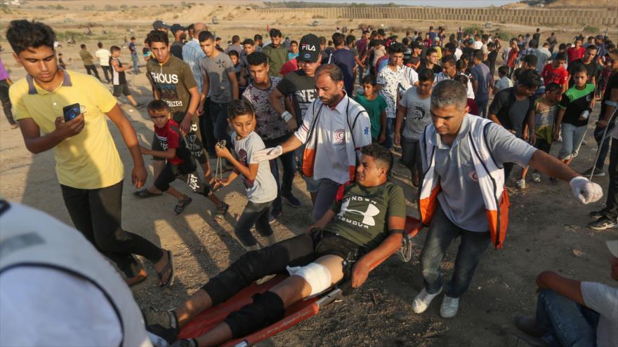 Palestinos trasladan a un joven herido por fuerzas israelíes en protestas en la Franja de Gaza, 20 de septiembre de 2019. (Foto: AFP)