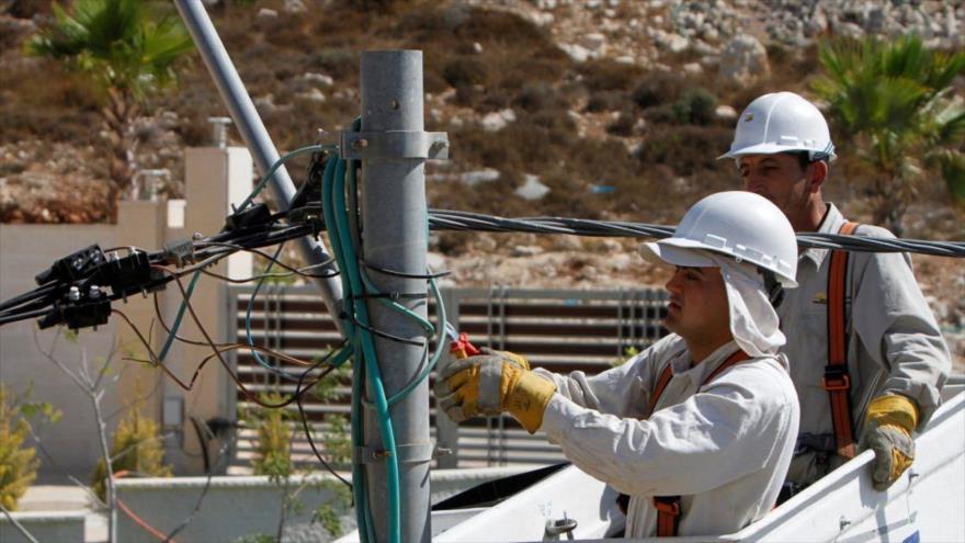 Electricistas instalan nuevas líneas de transmisión de energía en la ciudad cisjordana de Ramalá.