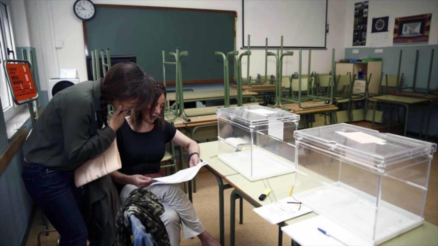 Dos mujeres revisan un listado electoral ante dos urnas vacías en un colegio electoral en España.