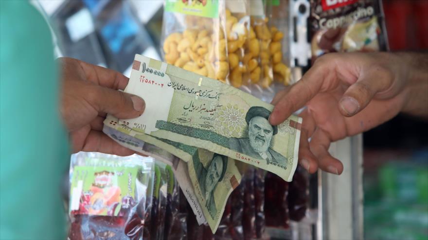Un hombre paga con moneda iraní en una tienda, en Teherán, capital, 31 de julio de 2019.
