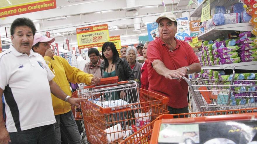 Unos hispanos hacen cola para comprar en la multinacional estadounidense Walmart.