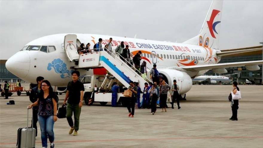 Pasajeros de un avión chino bajan de la aeronave tras aterrizar en un aeropuerto del país asiático.