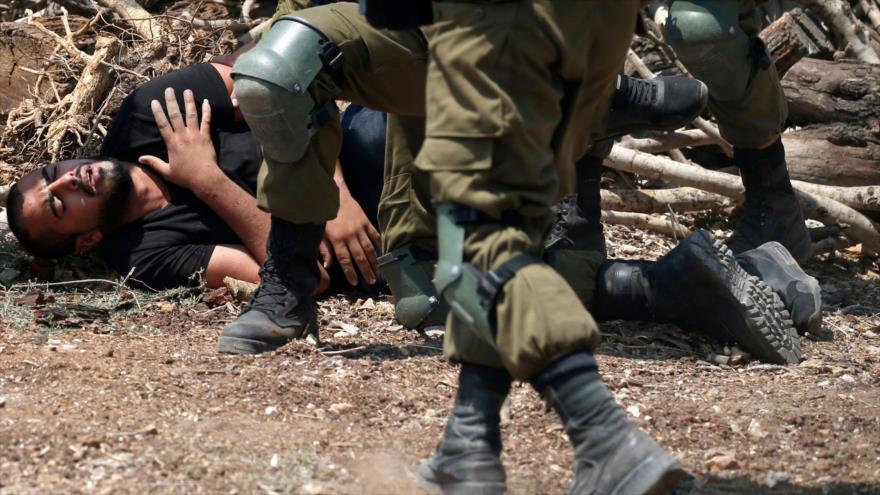 Soldados israelíes detienen a un palestino en la aldea de Kfar Qadum, en la Cisjordania ocupada, 23 de agosto de 2019. (Foto: AFP)