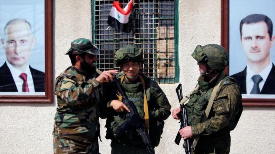 Dos militares rusos y un militar del Ejército sirio.