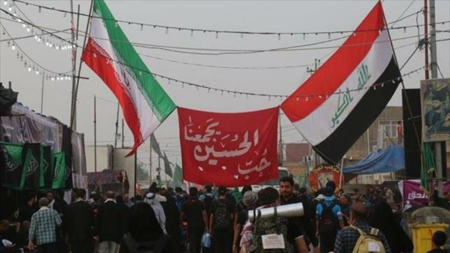 Los peregrinos de Arbain sostienen banderas de Irak e Irán mientras caminan entre las ciudades santas iraquíes de Nayaf y Karbala, octubre de 2018.