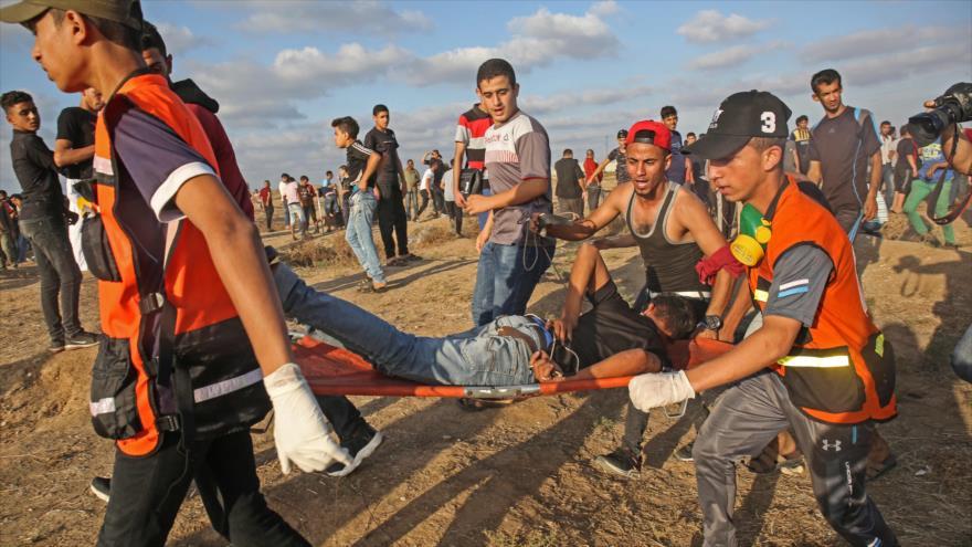 Llevan a un palestino herido por los disparos israelíes en los límites de Gaza y los territorios ocupados, 11 de octubre de 2019. (Foto: AFP)