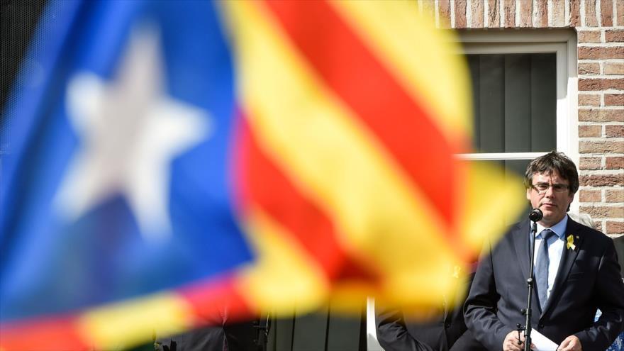 El expresidente de la Generalitat catalana Carles Puigdemont habla ante la bandera regional izada en Bruselas, capital belga, 28 de julio de 2018.