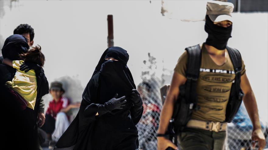 Las fuerzas kurdas escoltan a dos esposas de combatientes de EIIL en el campamento de Al-Hol, en el norte de Siria, 23 de julio de 2019.