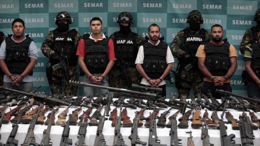 Varios miembros de un grupo de la delincuencia organizada de México posan detenidos delante de sus armas confiscadas procedentes de EE.UU., 6 de noviembre de 2018.