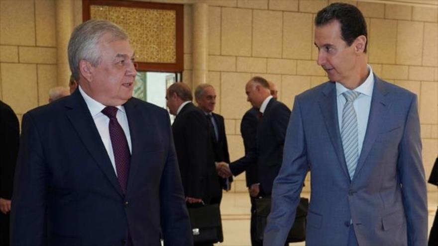 El presidente sirio, Bashar al-Asad (dcha.), y Alexander Lavrentiev, enviado especial del presidente ruso, en Damasco, capital siria, 18 de octubre de 2019. (Foto: SANA)
