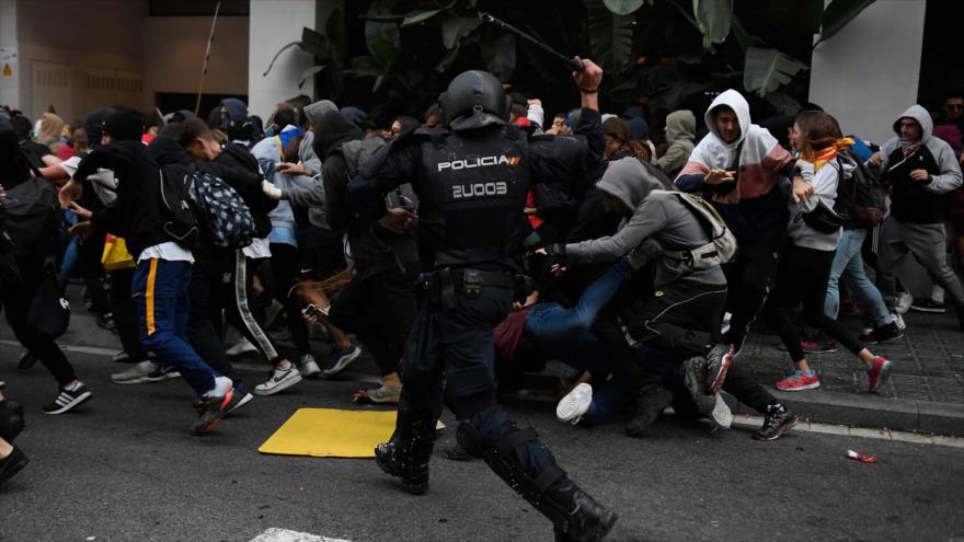 Un policía español reprimiendo a los manifestantes durante los enfrentamientos en Barcelona, 18 de octubre de 2019. (Foto: AFP)