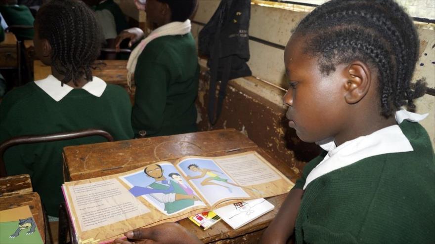 Una niña de edad escolar lee un libro en Kenia.