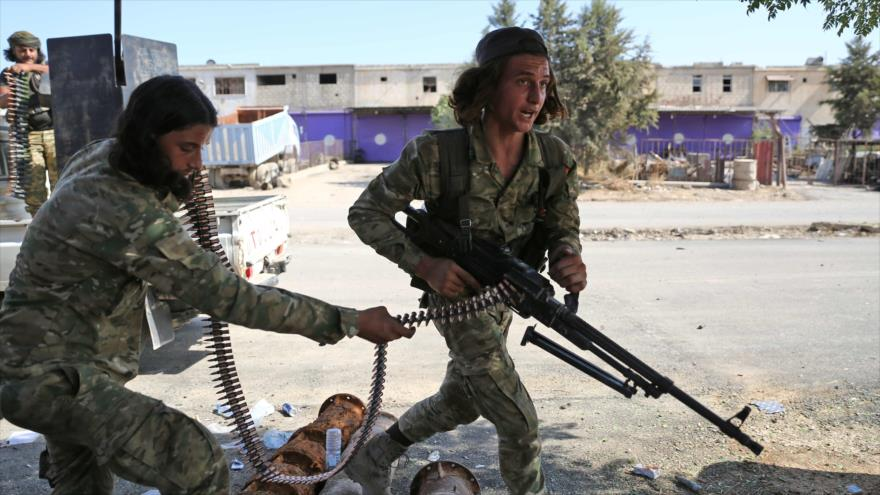 Dos milicianos armados en la ciudad de Ras al-Ain, en Al-Hasaka, 14 de octubre de 2019. (Foto: AFP)