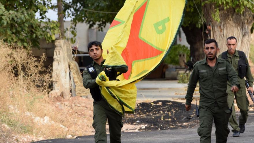 Fuerzas kurdas portan una bandera en la ciudad de Kobani, norte de Siria, 18 de octubre de 2019. (Foto: AFP)