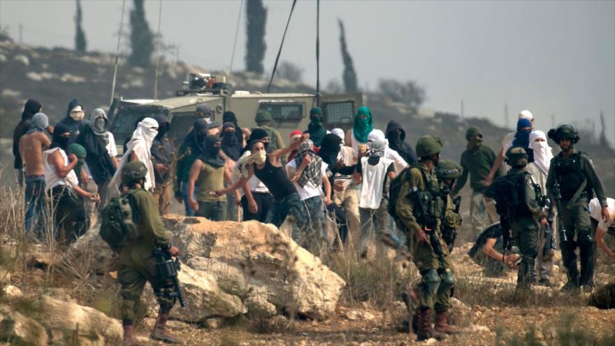 Colonos apoyados por soldados israelíes, lanzan piedras contra manifestantes palestinos en una aldea cisjordana, 17 de octubre de 2019. (Foto: AFP)