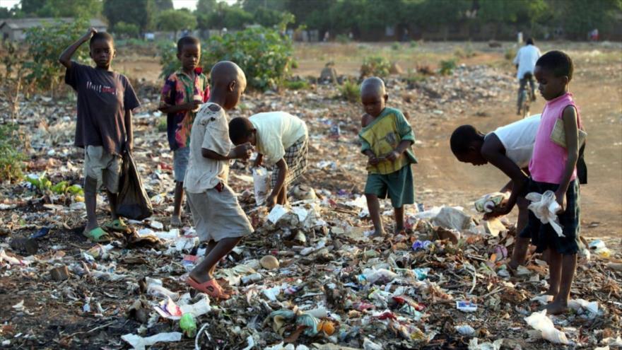 Varios menores africanos buscan comida entre la basura.