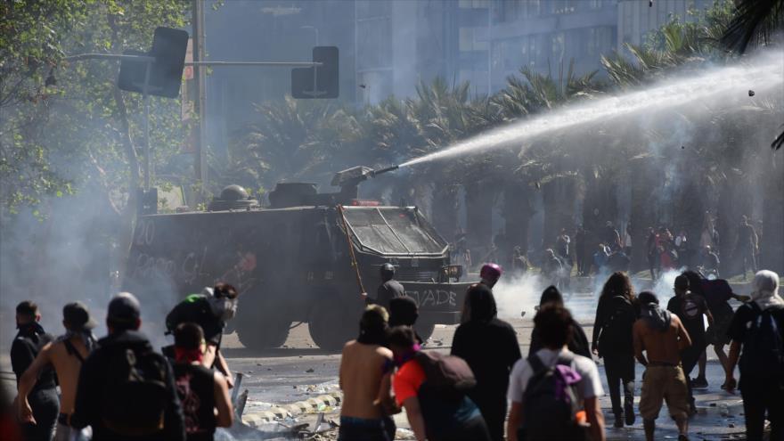 Policía de Chile dispara gases lacrimógenos contra los manfistantes en Satiago, la capital, 21 de octubre de 2019. (Foto: AFP)