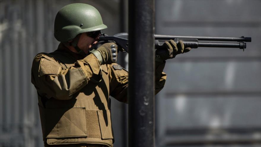Un policía apunta con su arma a los manifestantes durante las protestas en Santiago, capital de Chile, 21 de octubre de 2019. (Foto: AFP)