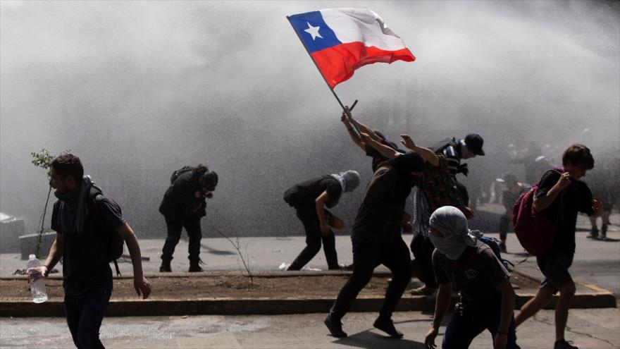 Los manifestantes se enfrentan con la policía antidisturbios en una protesta en Santiago, Chile, 21 de octubre de 2019 (Foto: AFP)