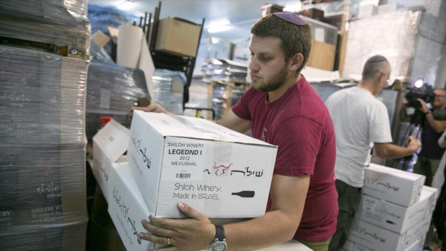 Un trabajador israelí sostiene cajas de productos fabricados en los territorios ocupados palestinos.