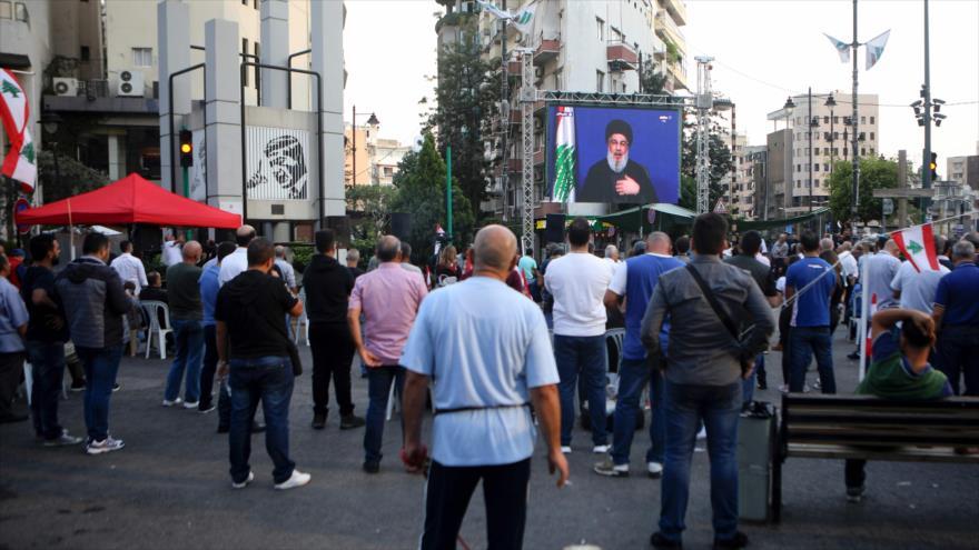 Una pantalla en una calle de Beirut difunde un discurso del líder de Hezbolá, Seyed Hasan Nasralá, por protestas en El Líbano, 25 de octubre de 2019.
