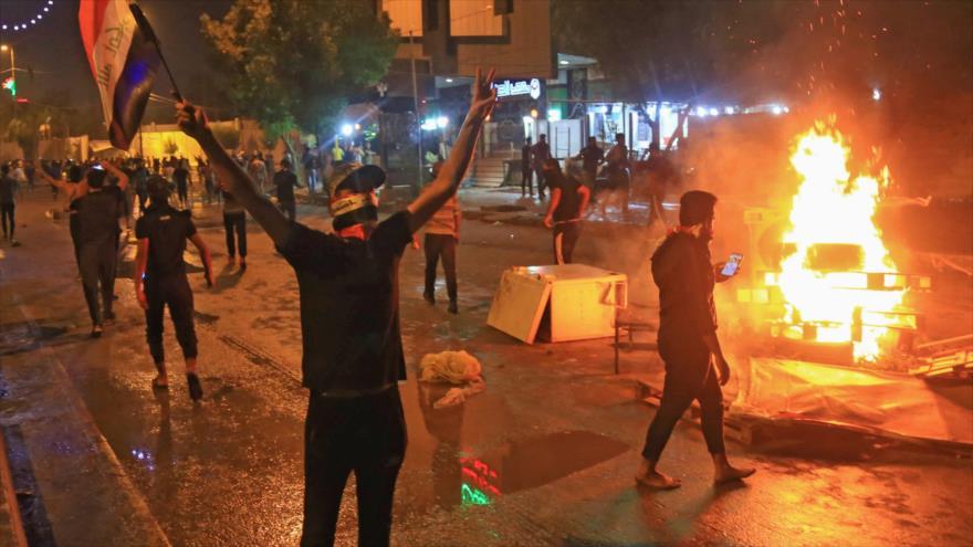 Varios manifestantes iraquíes prenden fuego en una localidad cerca de Bagdad, la capital, 25 de octubre de 2019. (Foto: AFP)