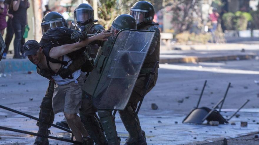 Agentes policiales de Chile detienen a un manifestante en Santiago (la capital), 24 de octubre de 2019. (Foto: AFP)