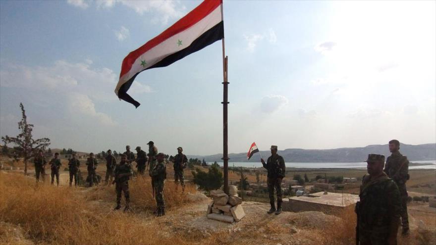 Soldados del Ejército sirio levantan la bandera de Siria cerca de los altos del Golán, ocupados por Israel, 27 de octubre de 2019. (Foto: AFP)